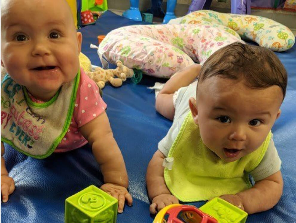 Two babies play with blocks and crawl toward the camera.