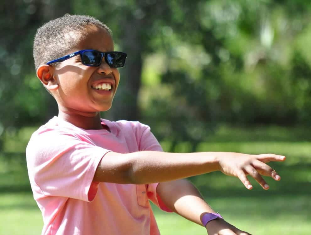 Elementary school boy with sunglasses plays outdoors at Child Care of Southwest Florida.