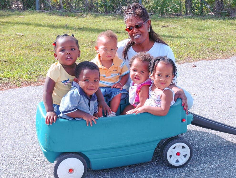 Five young toddlers post with their teacher while being pulled in a teal and black wagon outdoors.