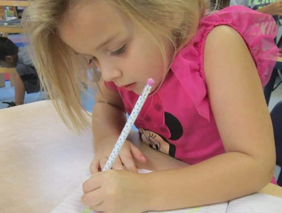 This studious young girl is improving her chance of success in school as she writes her homework with a pencil.