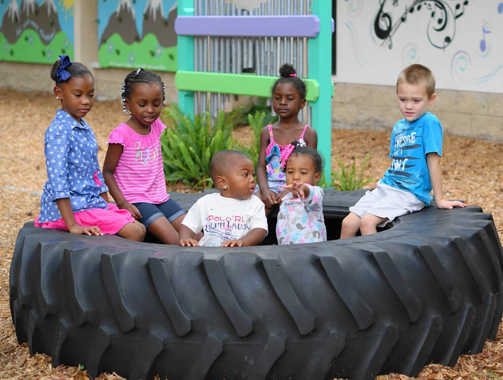 A group of six creative young children play outdoors in an old tire at Child Care of Southwest Florida.