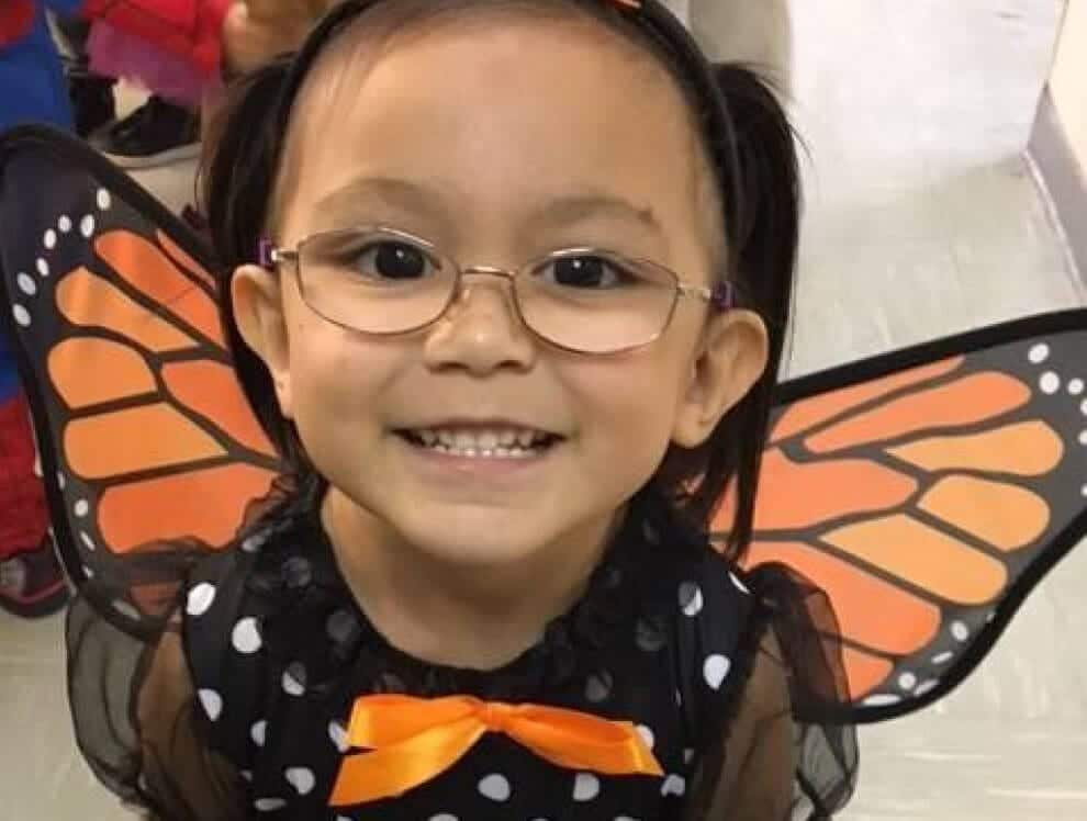 This young female student in glasses in a classroom setting while wearing butterfly wings.
