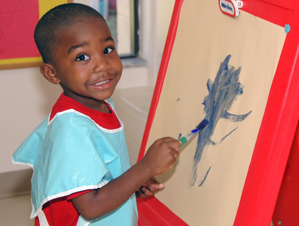 This young African-American boy uses a blue paintbrush during an enriching lesson at one of Child Care of Southwest Florida's five affordable early childhood learning centers.