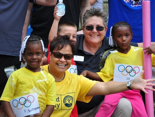 Two young girls in yellow shirts pose with United Way representatives at a Child Care of Southwest Florida event.