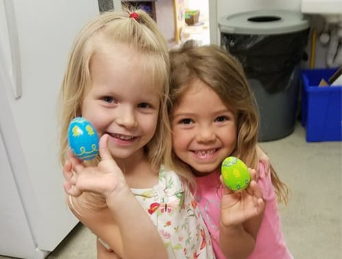 Two girls play with Easter eggs at Child Care of Southwest Florida.