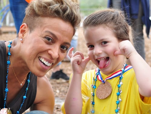 Goofy girl and child care leader play outdoors at sport event at Child Care of Southwest Florida