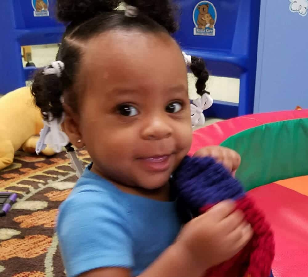 Smiling African-American girl enjoys toys in playroom at Child Care of Southwest Florida.