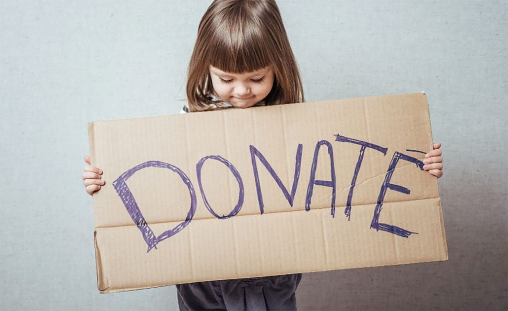 Young girl holds Donate sign for Hurricane Dorian