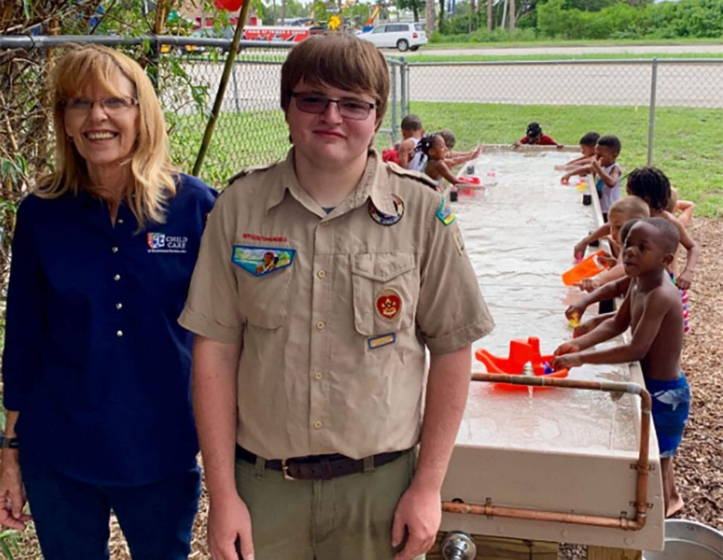 Eagle Scout Kyle W and Tamara Aronson with children playing with water table in the background.