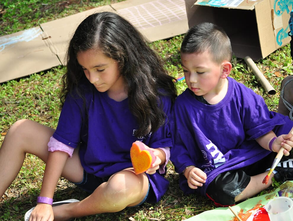 Two kids in purple shirts enjoy outdoor learning assignments based on each child's academic interests and needs.