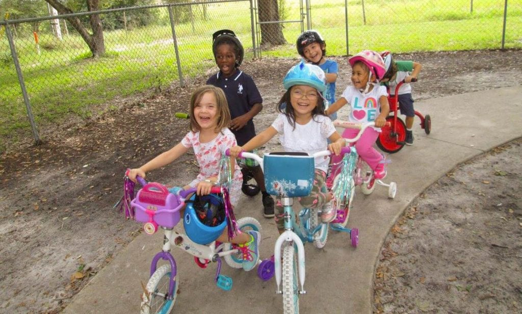 This group of six happy children engages in active learning while riding bicycles outdoors.