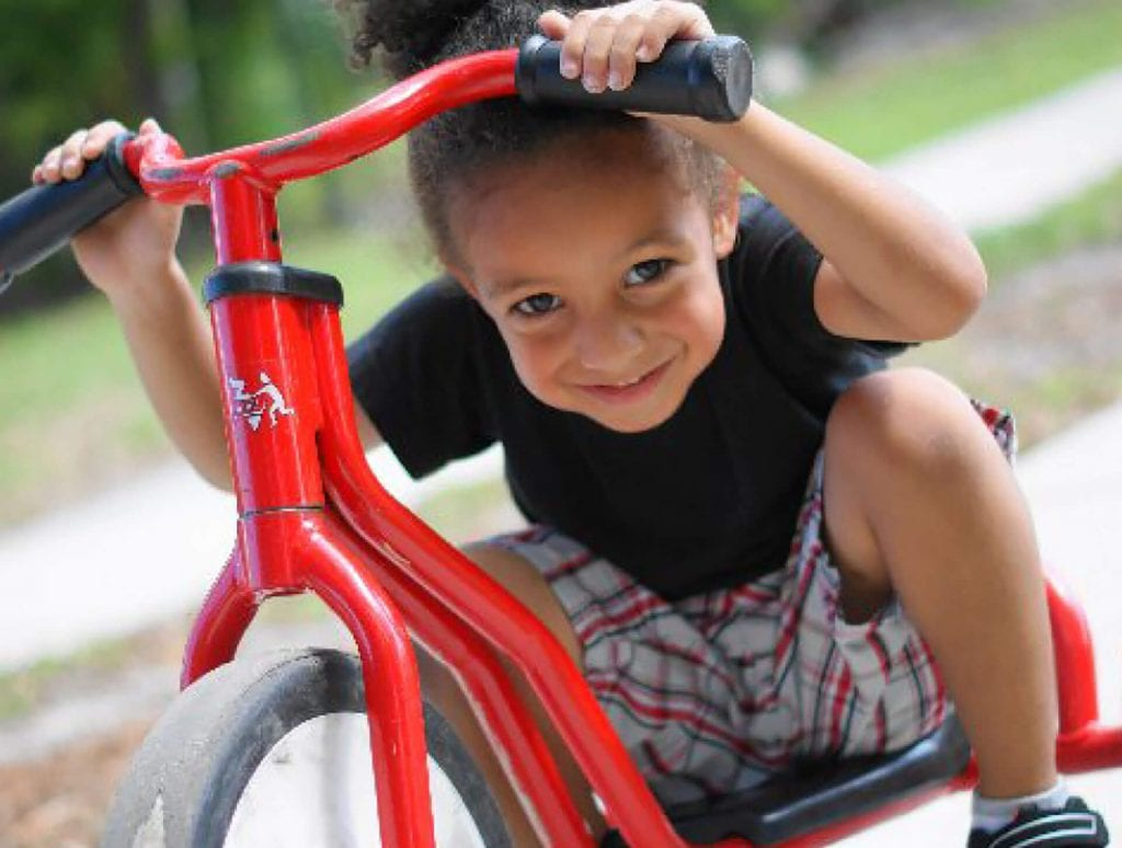Young African-American female with black Tshirt and plaid shorts sits on red tricycle bike.