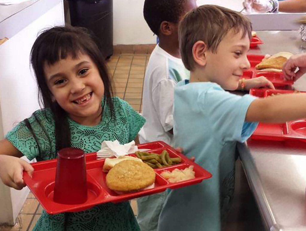 Two children smile while picking up their lunches at Child Care of Southwest Florida.