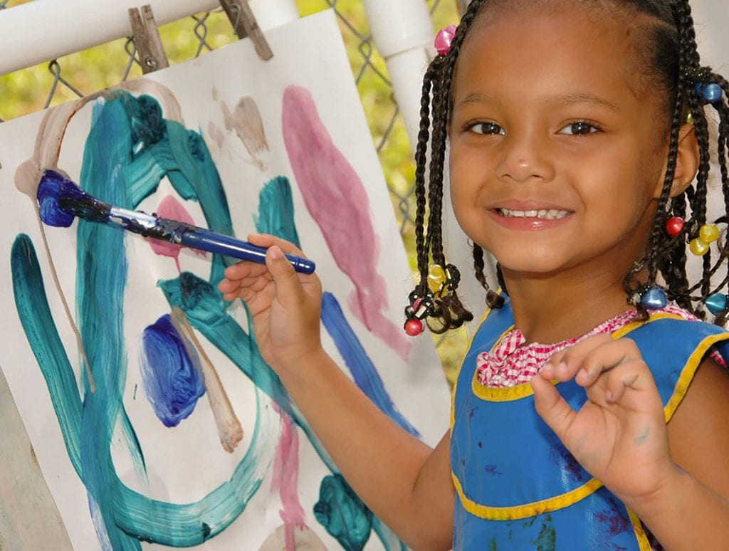 Your gift to Child Care of Southwest Florida will provide an education for a child in need, much like this young girl painting in her classroom.