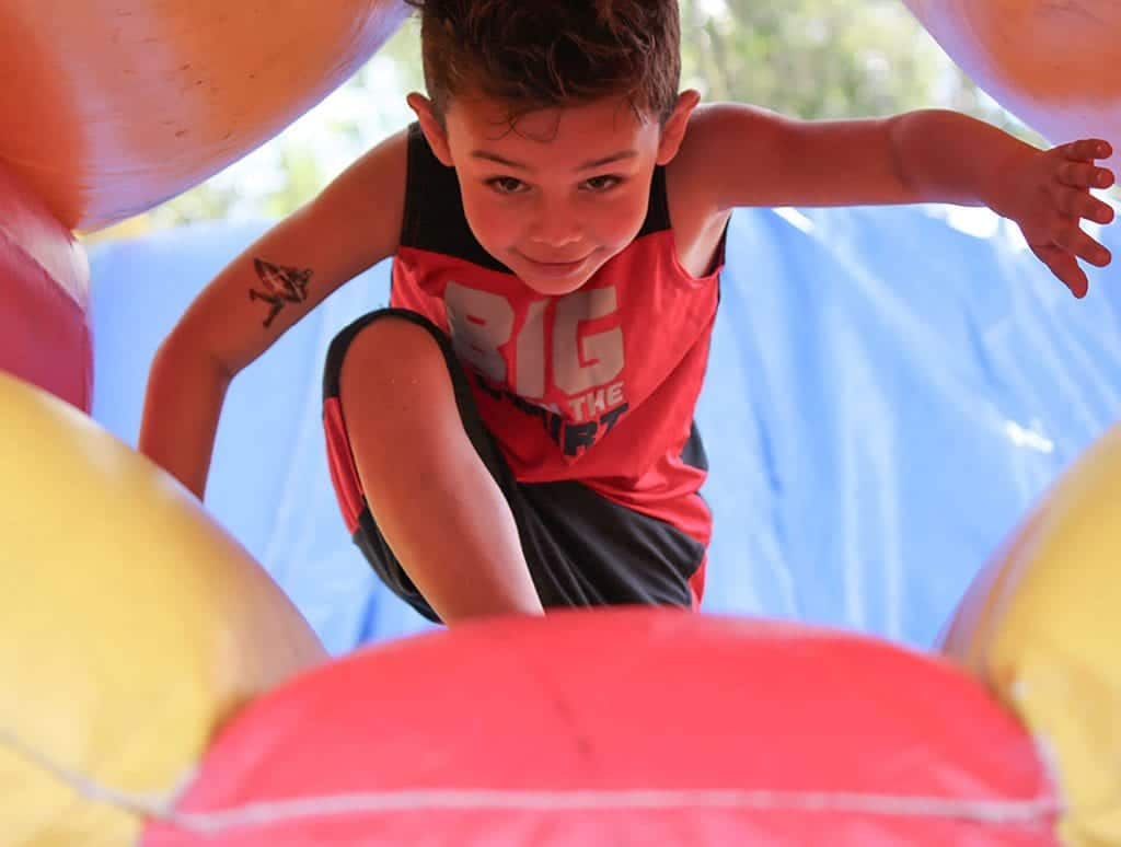A boy runs through a bounce house at Child Care of Southwest Florida.