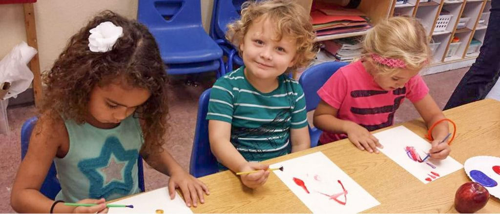 Three Child Care of Southwest Florida students create artwork with paintbrushes as one smiles at the camera.