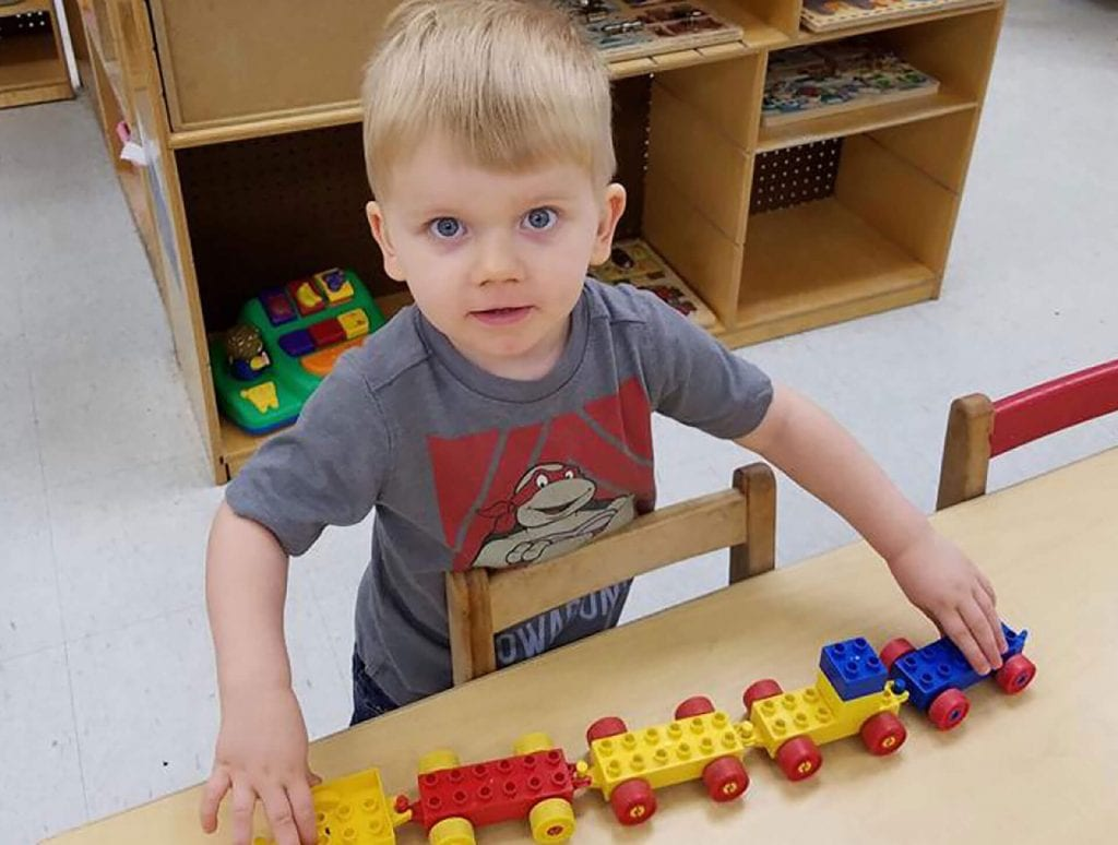 This young Child Care of Southwest Florida male student plays with a toy train in his classroom.