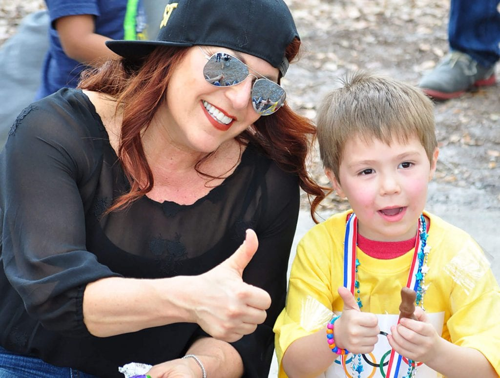 Energetic volunteer with child outdoors at Child Care of Southwest Florida