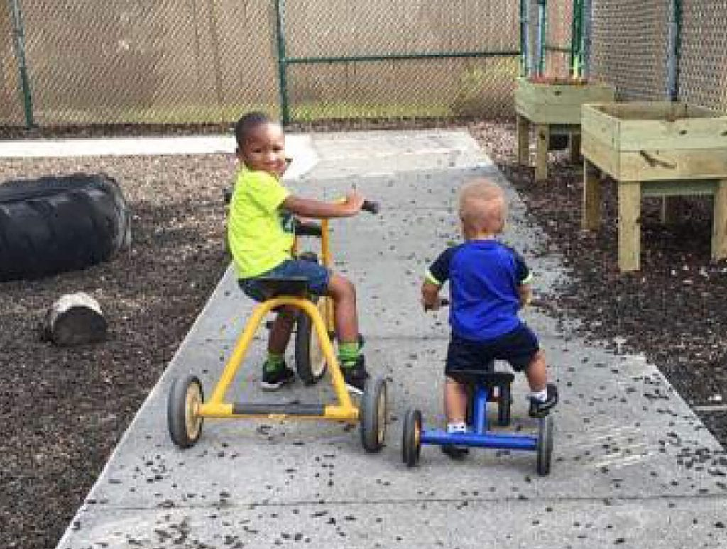 These two boys ride bicycles through the courtyard at Child Care of Southwest Florida.
