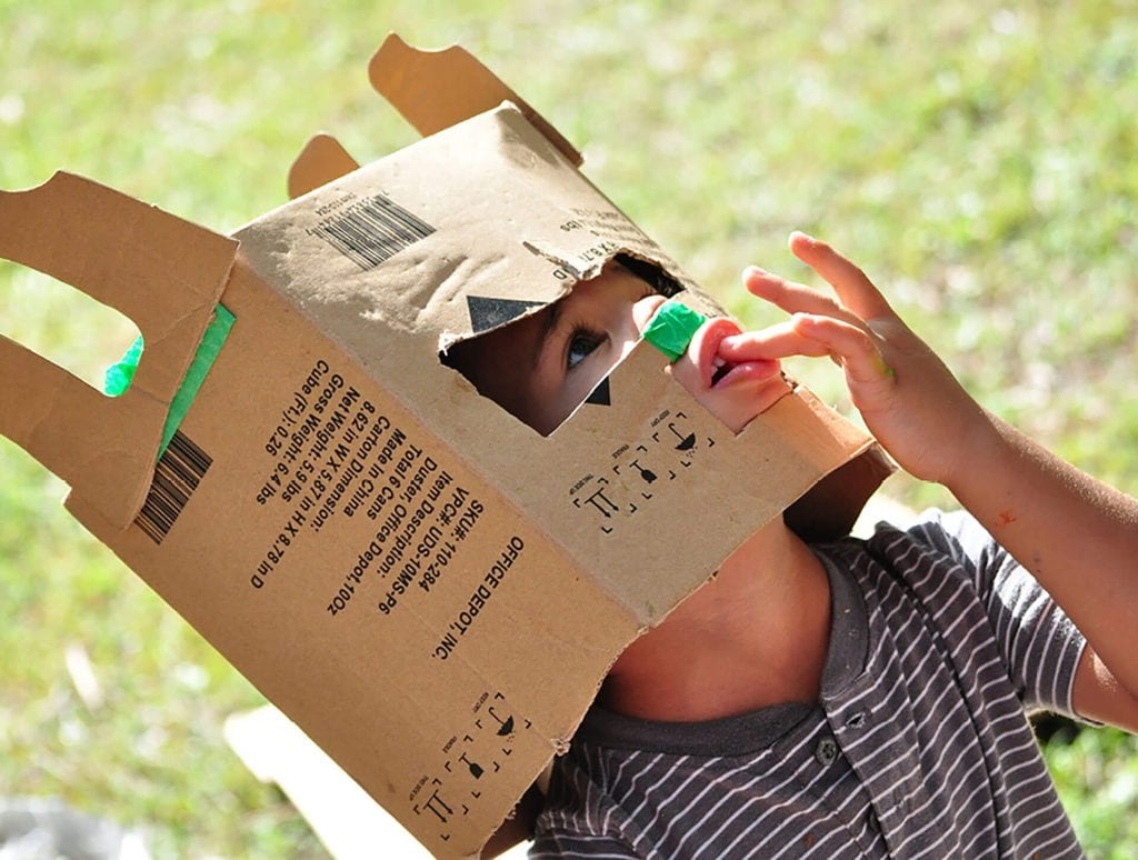 Young boy engages in a play-based learning activity with a paper bag mask.