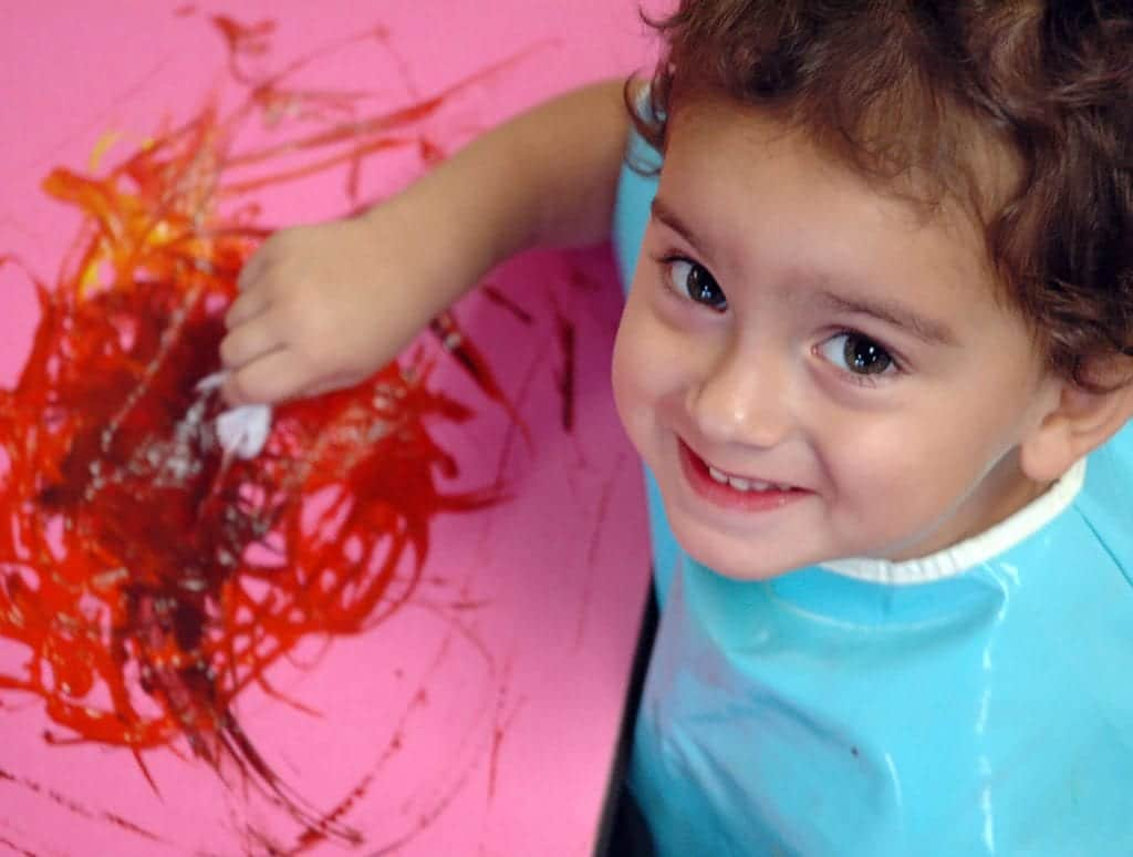 It's proven that children learn by playing, which is why this young child is using red fingerpaint during an early childhood learning experience at Child Care of Southwest Florida.