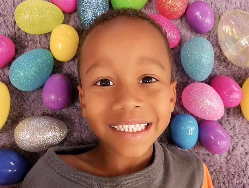 Cute young African-American boy lays in a pile of Easter eggs at his Child Care of Southwest Florida's early childhood learning center.
