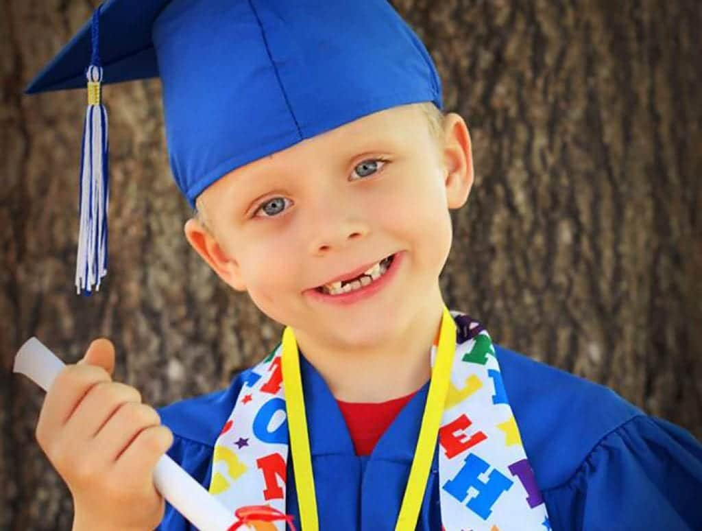 This young boy in a blue graduation cap with his diploma celebrates his academic success.