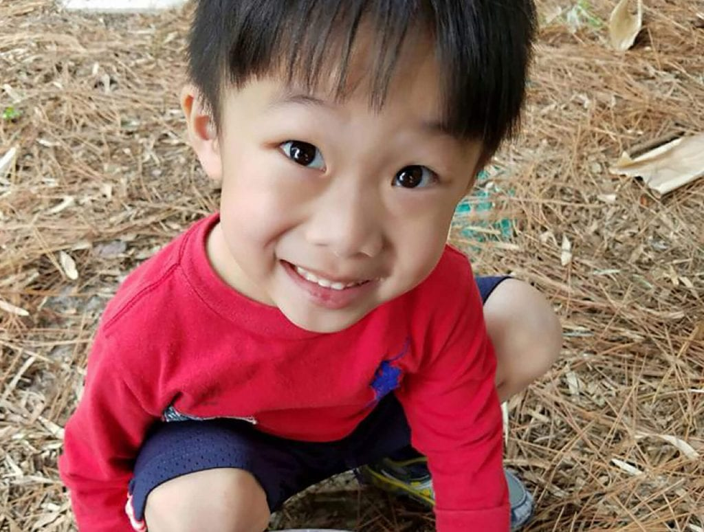Young Asian boy smiles up at the camera while sitting on pine needles