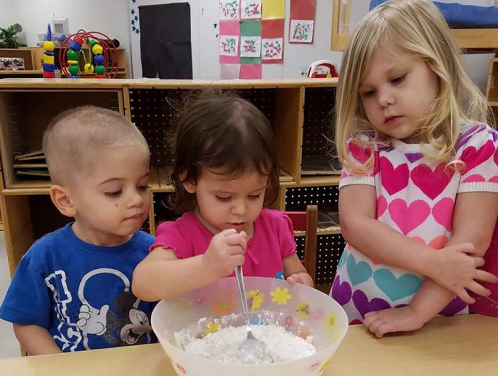 A young boy and two young girls mix a cake during a cooking class