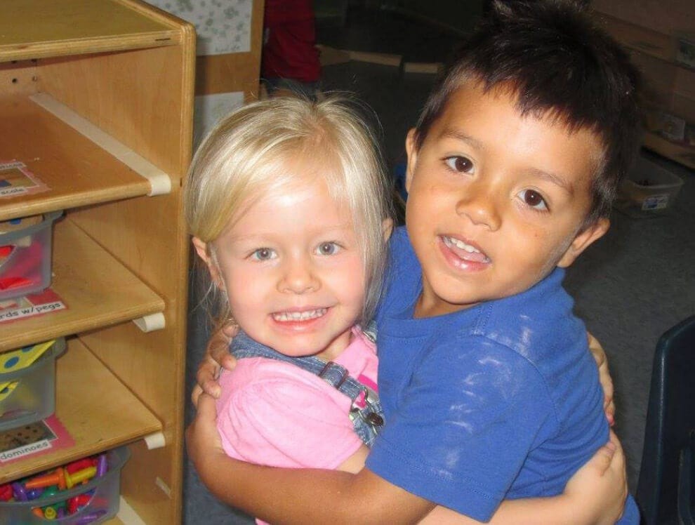 Two young friends hug in a classroom at one of Child Care of Southwest Florida's affordable early childhood learning centers since 1968.