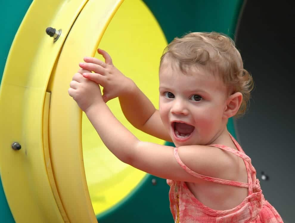 A young toddler girl at Child Care of Southwest Florida gets on the outdoor playground slide with a big smile.