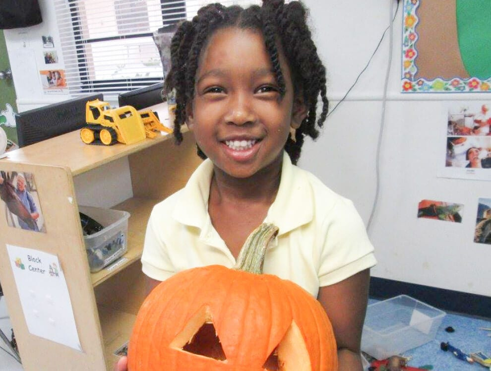 This young African American girl holds up a creatively carved pumpkin in her Child Care of Southwest Florida classroom.