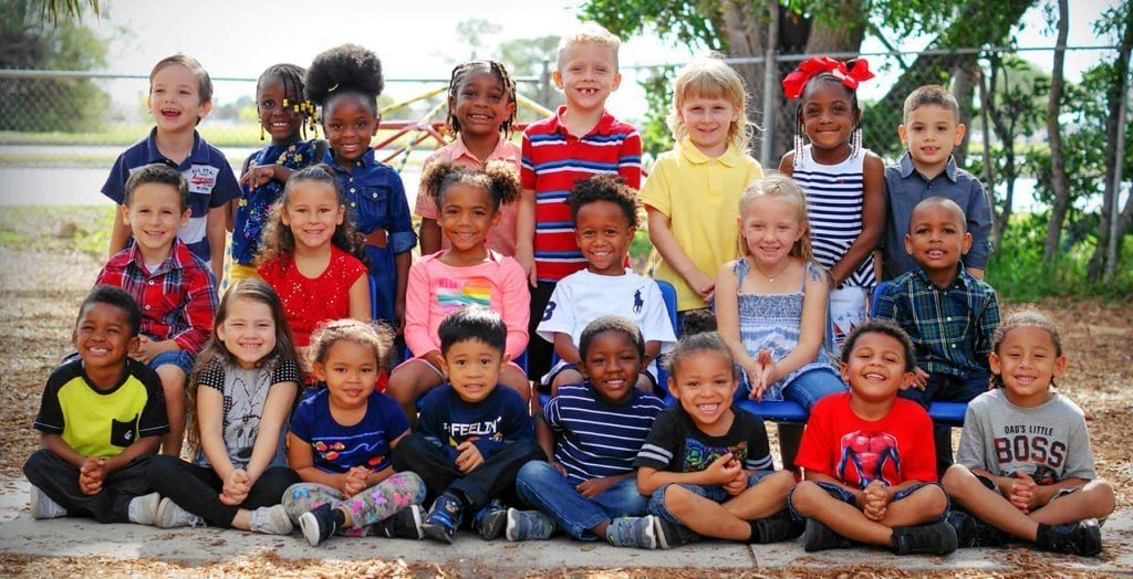 A total of 20 children split into 3 rows pose for their end-of-year school photo with big, beaming smiles