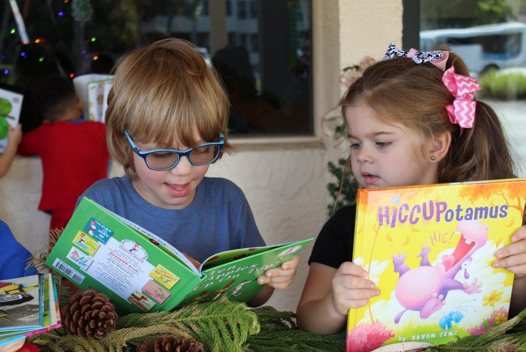 two children reading books at literacy parade